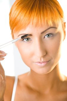 Red-haired Woman Making Her Makeup Stock Images