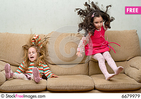 Two little girls jumping on sofa Stock Photo