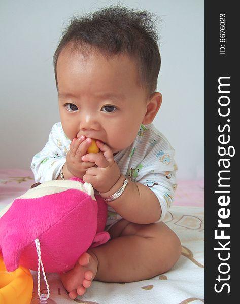 Lovely baby eating toys