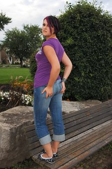 Girl Standing On Park Bench. Stock Photos