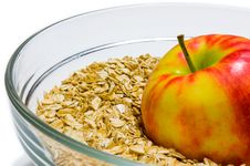 Apple On Oat Flakes Background In A Glass Bowl &x28;front View&x29; Stock Images