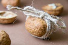 Walnut Tied With Twine On The Blurred Background On A Brown Stock Photo