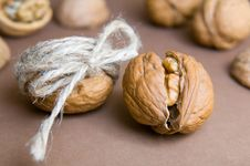 Walnut Tied With Twine And Cracked Walnut On The Background Of O