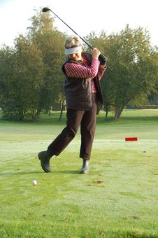 Female Golfer Teeing Off Stock Image