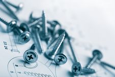 Metal Screws Over Technical Drawing Royalty Free Stock Photos