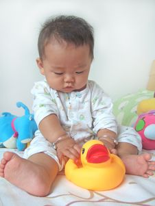Pretty Baby And Toy Ducks Stock Photos