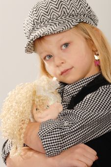 Cute Blonde Girl In Cap With Doll Stock Photos