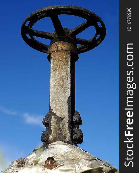 Industrial pipe valve against blue sky