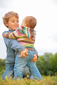 Free Boy Embraces Child On Grass Stock Image - 6792411