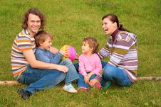 Free Family Of Four Sits On Grass Stock Images - 6792884