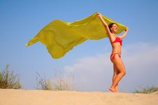 Young Girl On Sand With Yellow Shawl In Hands Stock Photography