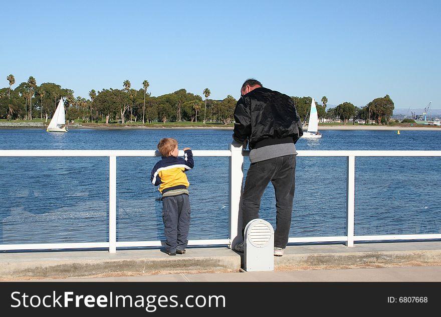 Boy and man looking at bay water