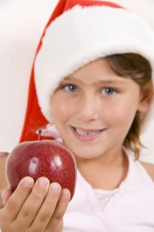 Free Girl Wearing Christmas Hat And Holding An Apple Stock Photos - 6810763