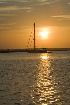 Sailboat At Sunset In Coastal Harbor