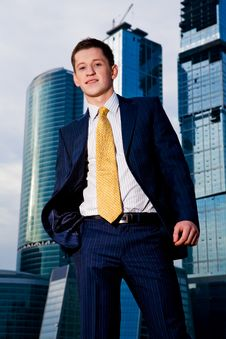Friendly Businessman Standing Against Skyscraper Stock Photography