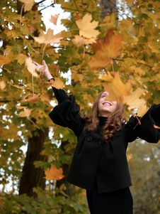 Youn Girl Throws Leaves Upwards In Forest. Royalty Free Stock Images