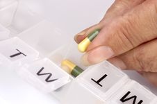 Free A Hand Sorting Capsules To A Pill Dispenser Stock Image - 6932461