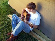 Free Boy Relaxing Playing Guitar Royalty Free Stock Image - 7014356