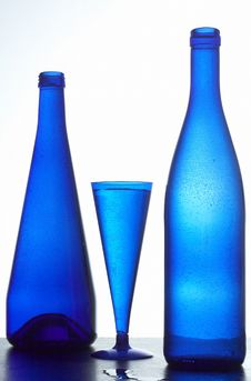 Two Dark Blue Bottles And Glass Royalty Free Stock Image