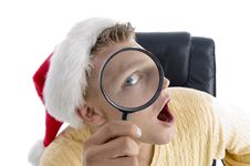 Man Wearing Santa Hat And Looking Through Lens Royalty Free Stock Photos