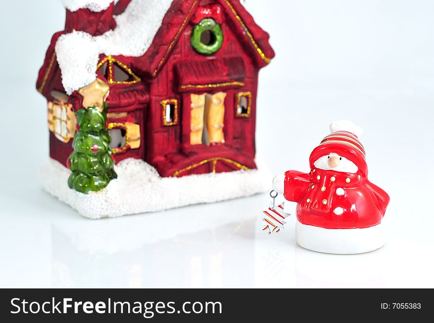 Funny little snowman with small house in the back
