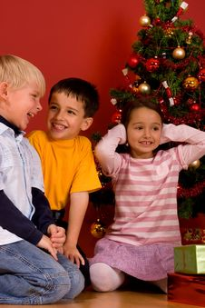 Children Sitting By Christmas Tree Royalty Free Stock Images