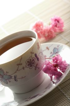 Cup Of Tea And Flowers Over Bamboo Mat Royalty Free Stock Photos