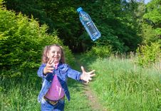 Girl Catching A Plastic Bottle Stock Images
