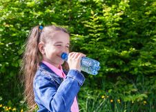 Free Girl Drinks Water From A Plastic Bottle Royalty Free Stock Photography - 72185997