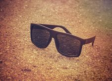 Free Black Sunglasses On The Beach In The Morning Royalty Free Stock Photography - 73951917