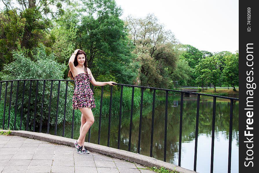 Beautiful brunette standing on the bridge near the river