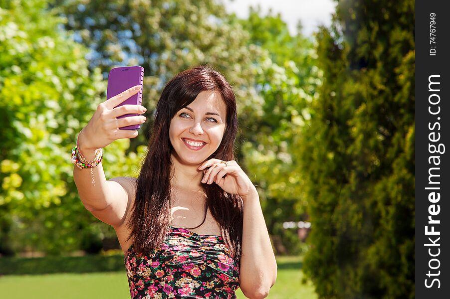 Girl doing selfie mobile phone in park