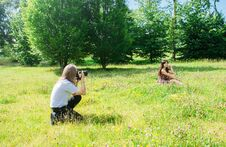 Photographer Takes A Woman Sitting On The Grass In The Park Royalty Free Stock Images