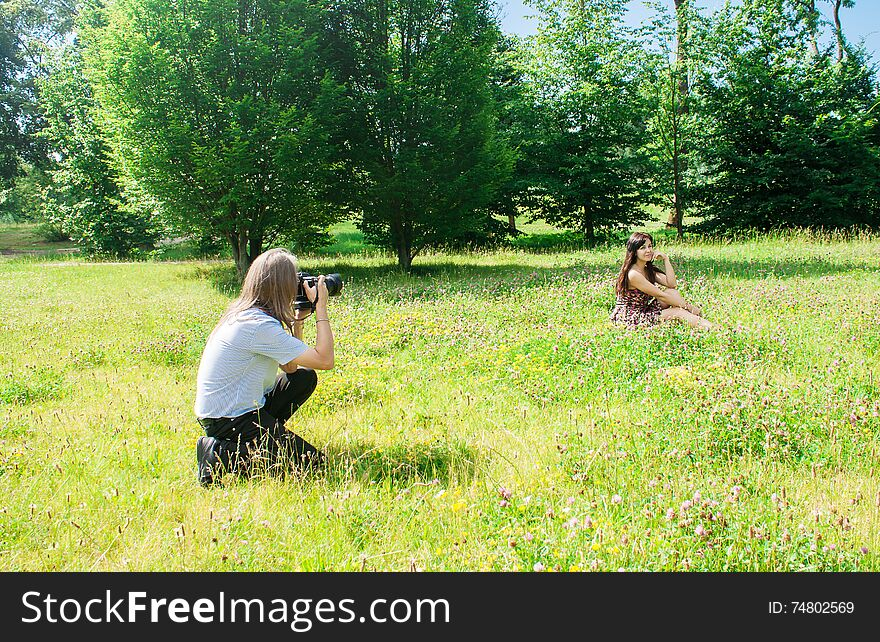 Photographer takes a woman sitting on the grass in the park