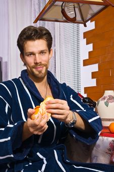 Free Young Man In Bathrobe In Kitchen Peels Tangerine Royalty Free Stock Images - 7586049