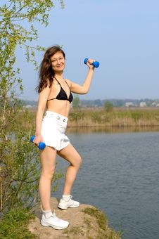 Young Woman With Weights Exercising Outdoors Stock Image