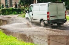 Free Commercial Vehicle Rides On Big Puddle On The Road Stock Images - 76449064