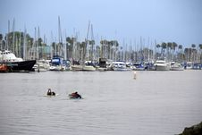 Free Surfers Paddling Through Boat Harbor Jetty Stock Photography - 771252