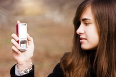 Young Beauty Looking At Her Cell Phone Stock Images