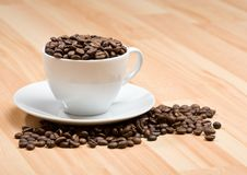 Cup With Freshly Roasted Coffee Beans On Floor Royalty Free Stock Photography