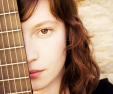 Free Woman Behind Guitar Fretboard Stock Photography - 7708552