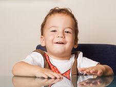 Free Small Boy Sitting At A Table Stock Photos - 7716753