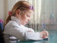 Free Small Girl Is Writing With A Pen Stock Image - 7716781