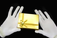 Free Hands In White Gloves With A Golden Gift Royalty Free Stock Photos - 7732878