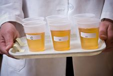 Amber Liquid In Plastic Cups On Plate Stock Image