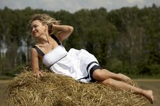 Lovely Smiling Woman Lying On Haystack Outdoors Stock Photos