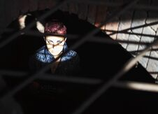 Free Punk Girl Sitting On The Floor Behind Metal Bars Stock Photography - 77446192