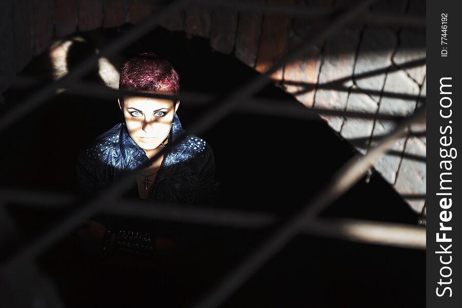 Punk girl sitting on the floor behind metal bars
