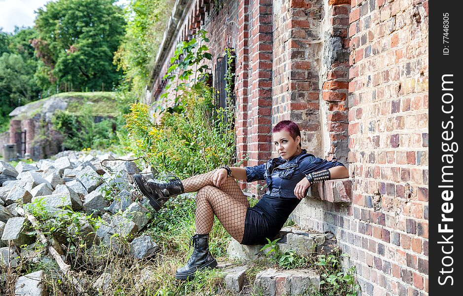 Punk girl sitting on the porch of an old castle