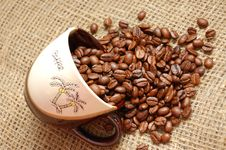 Coffe Beans Strewed From Cup Into Sacking Royalty Free Stock Image